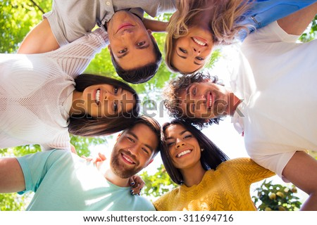 Group of friends hugging together at the park in a circle - stock photo