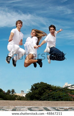 Group of friends in a jump against a city and the sky - stock photo