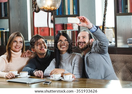 Group of friends in cafe taking photos on smartphone - stock photo