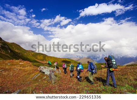 group of friends in hiking in high mountains.  snow-capped peaks, glaciers and  Fantastic sky background with blue clouds. Beautiful world - stock photo