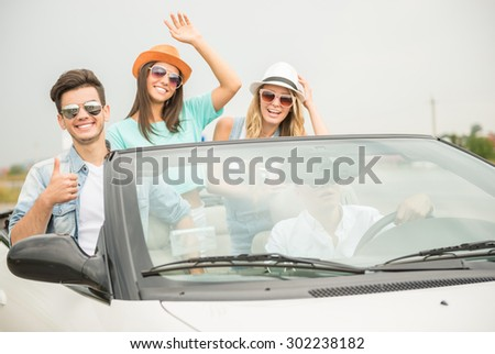 Group of friends in sunglasses traveling on the cabriolet and having fun. - stock photo