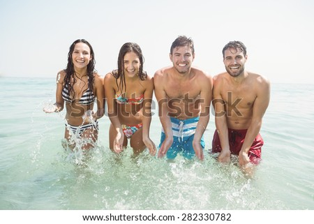 group of friends in swimsuits at the beach