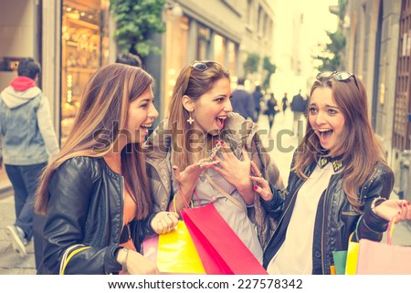 group of friends in the city center making shopping. one girl showing new bracelet and her friends are very impressive - stock photo