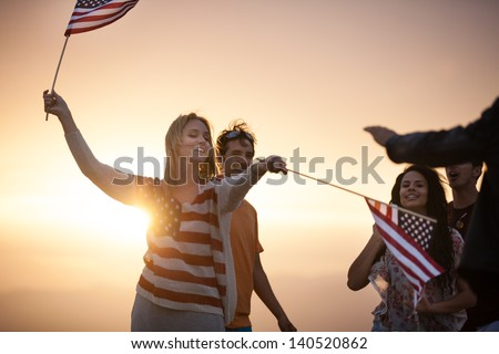 Group of Friends in their twenties dancing on the Beach at Sunset in California - stock photo