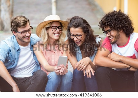 Group of friends interacting using mobile phone - stock photo