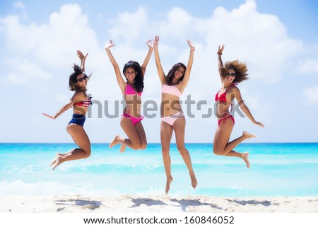 Group of friends jumping at a tropical beach  - stock photo