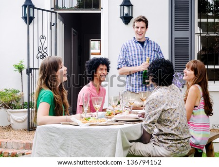 Group of friends laughing at a joke in the speech before champagne is popped and poured - stock photo