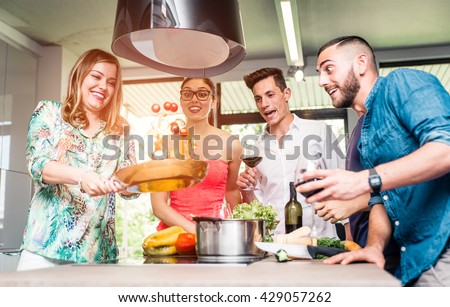 Group of friends making pasta party and having fun in the kitchen - stock photo