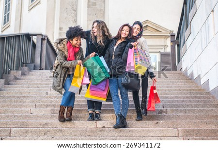 group of friends making shopping together. mixed race girls with shopping bags. they are a caucasian one, an asian, an african and one arabian - stock photo