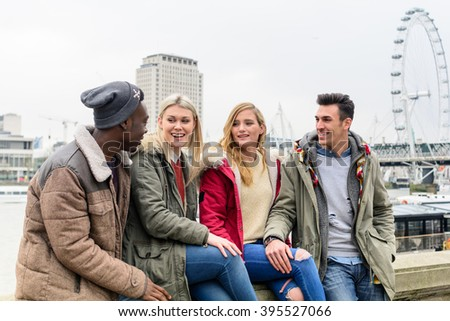 Group of friends meeting in the city and talking together with urban background and London Eye. Communication discussion unity concept about four happy friends smiling to each other and sitting. - stock photo