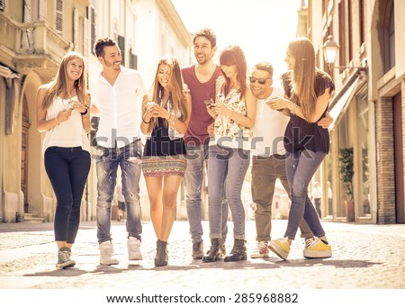 group of friends meeting in the city center. they are having fun with smart phones and walking together - stock photo