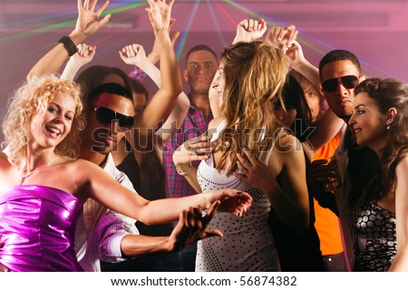 Group of friends - men and women of different ethnicity - dancing to the music in a disco club having lots of fun - stock photo
