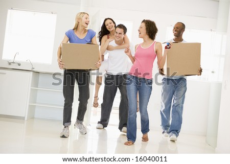 Group of friends moving into new home smiling - stock photo