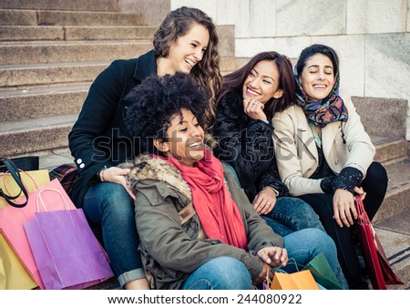 group of friends of different ethnicity sitting on the stairs and having fun - stock photo