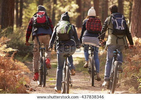 Group of friends on bikes in a forest, back view close up - stock photo