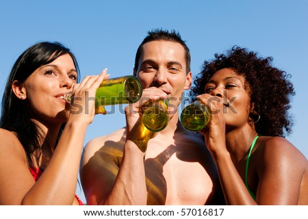 Group of friends - one man embraces two women and all have drinks in swimwear on the beach of a lake in summer - stock photo