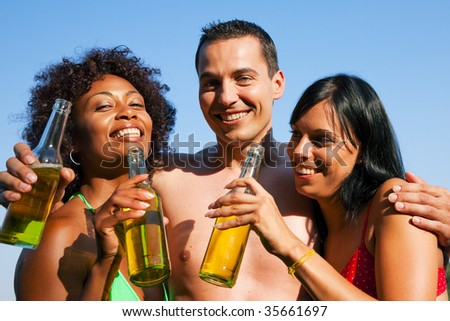 Group of friends - one man hugs two women and all have drinks in swimwear - stock photo