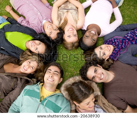 group of friends or college students outdoors with heads together - stock photo