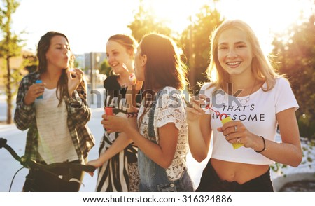 Group of friends outside hanging out and laughing - stock photo