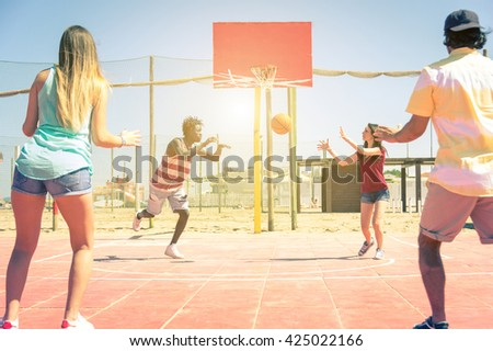 Group of friends playing basketball - Group of sportive multiracial people playing togheter during the summertime  - Concept about people, lifestyle and sport - stock photo