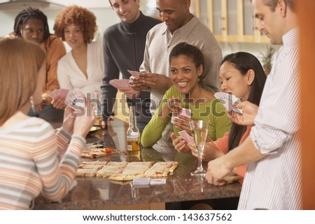 Group of friends playing cards at a party - stock photo