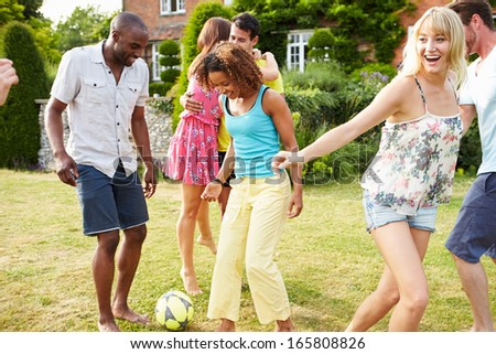 Group Of Friends Playing Football In Garden - stock photo