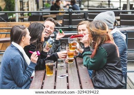 Group of friends playing some paper trumpets. They are outdoor, at pub, drinking beer. They are having a small party and everybody is happy.