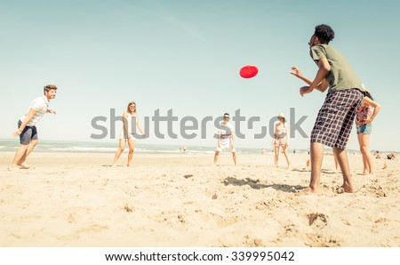 Group of friends playing with frisbee on the beach