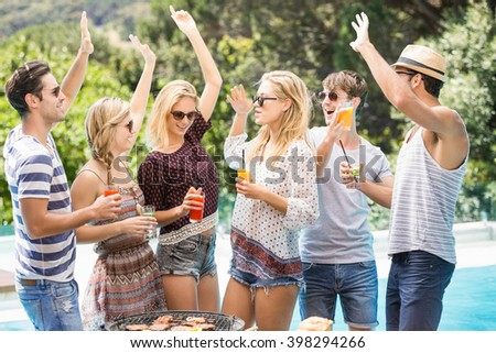 Group of friends raising their hands and enjoying near pool - stock photo