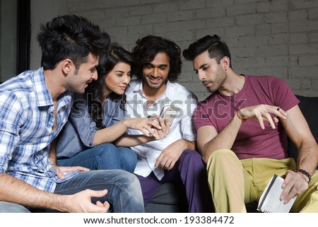 group of friends reading a message on smart phone. - stock photo