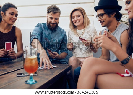 Group of friends relaxing and playing cards together. Young people hanging out together around a table during a party playing a game of cards. - stock photo
