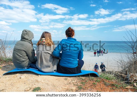 Group of friends relaxing on the coast in winter or early spring. - stock photo