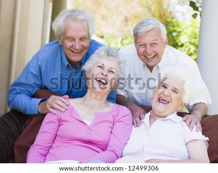 Group of friends relaxing sitting on garden seat - stock photo
