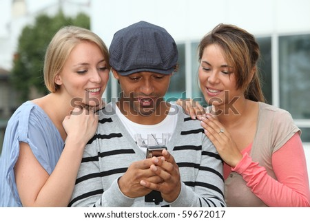 Group of friends sending message with mobile phone - stock photo