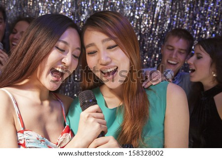 Group of friends singing into microphone at karaoke