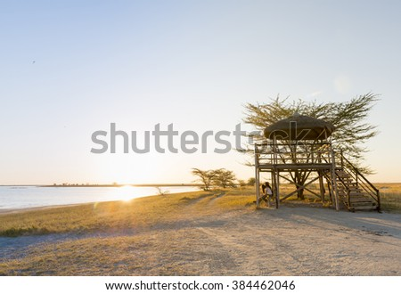 Group of friends sit relaxing at sunset on the beach under a large open air hut in Africa - stock photo