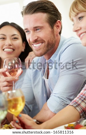 Group Of Friends Sitting Around Table Having Dinner Party - stock photo