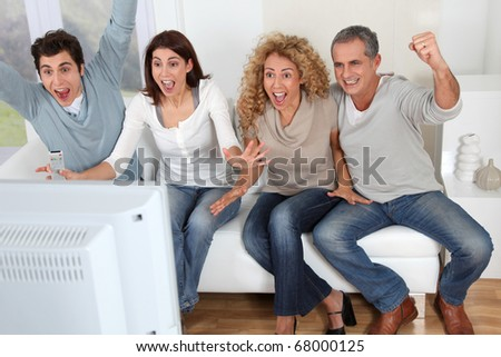 Group of friends sitting in sofa watching sport game on tv - stock photo