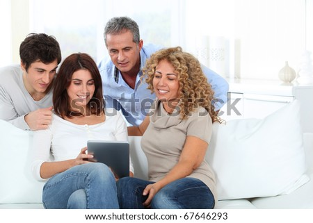 Group of friends sitting in sofa with electronic tab - stock photo