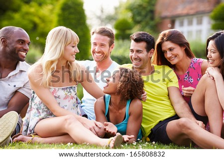 Group Of Friends Sitting On Grass Together - stock photo