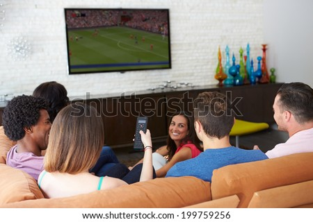 Group Of Friends Sitting On Sofa Watching Soccer Together - stock photo
