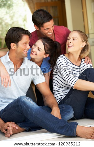 Group Of Friends Sitting Outside House