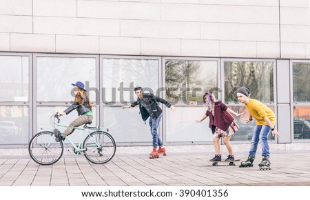 Group of friends skating and cycling in an urban area - Cheerful teenagers having fun outdoors - stock photo