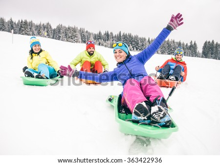 Group of friends sledding on snow - Four tourists on winter vacation