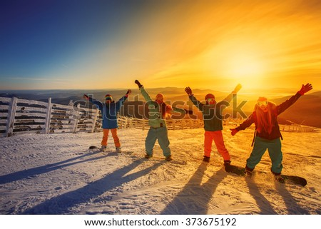 Group of friends snowboarders having fun on the top of mountain in Sheregesh resort - stock photo