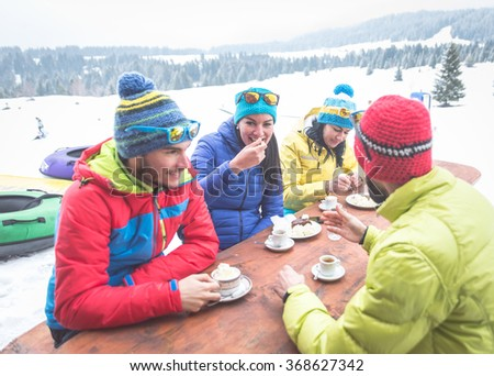 Group of friends spending time together. Having a break in a mountain chalet after skiing. Concept about winter vacation and friendship - stock photo
