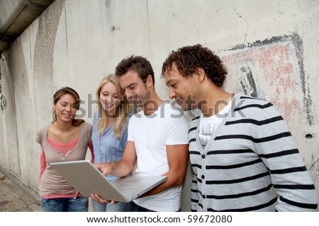 Group of friends standing against wall with laptop computer - stock photo