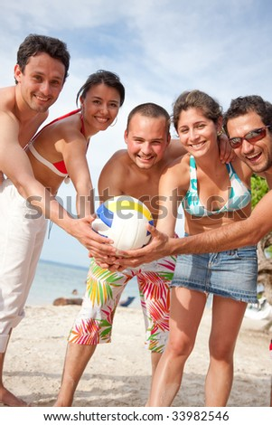 Group of friends standing at the beach with a ball - stock photo