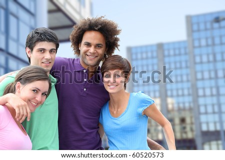 Group of friends standing in front of modern buildings in  town - stock photo