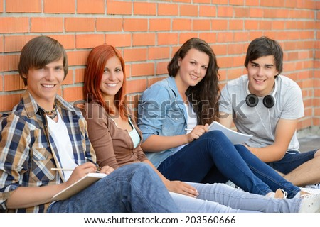 Group of friends students sitting in row against brick wall - stock photo